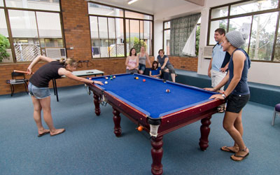 Students playing pool in the common area